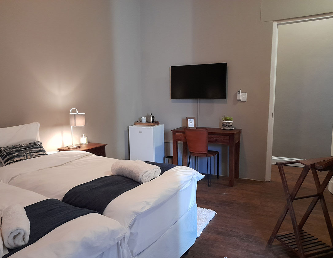 Suite 2 Safari Villa rental with two single beds, a writing desk, and a chair in Windhoek, Namibia