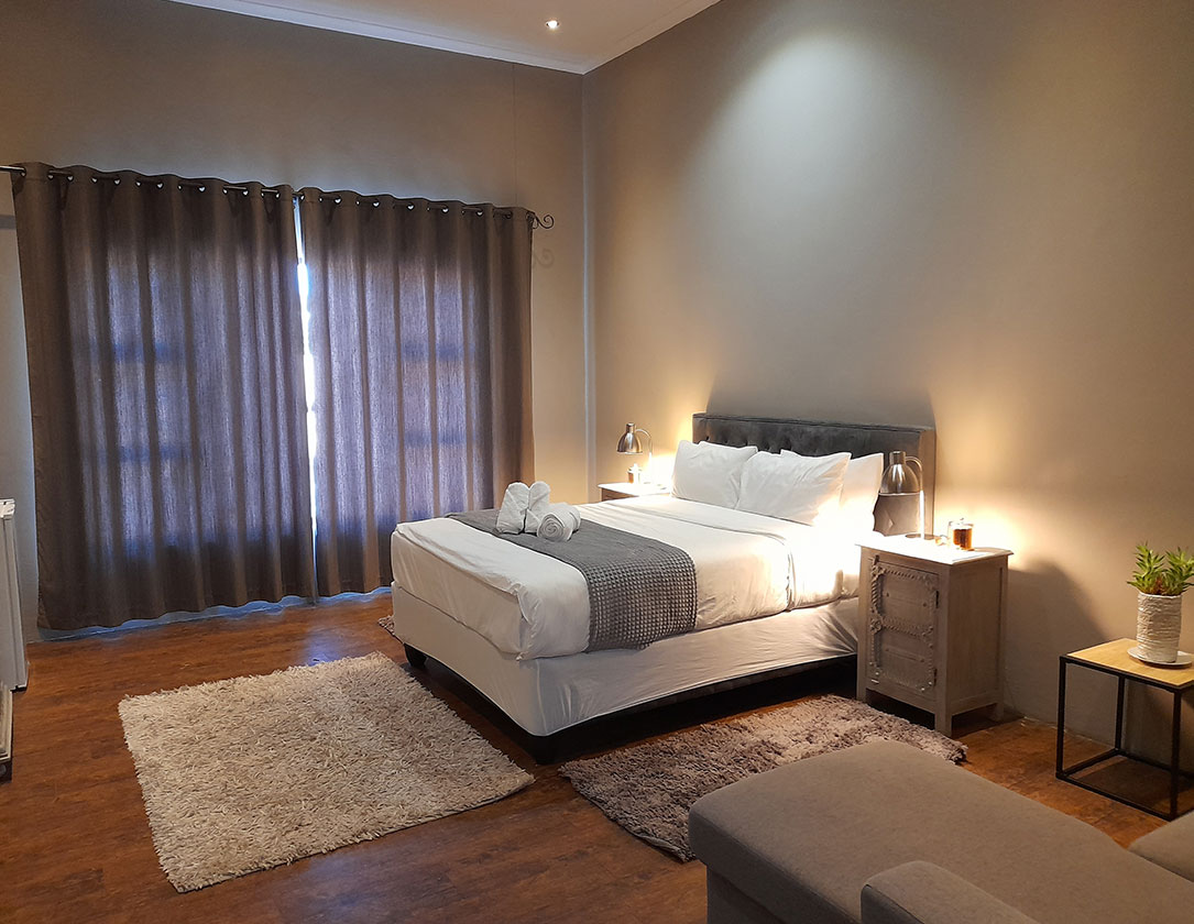 Suite 3 Safari Villa rental with a Queen-size bed, a sofa bed, and sitting area in Windhoek, Namibia.